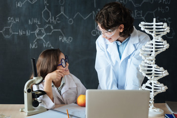 Cheerful little pupils working on the science project at school