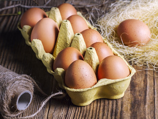 Eggs, hay, jute rope on a wooden table