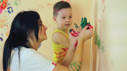 Happy mother and her cute boy having fun together leaving their colorful handprints and painting on the wall. Young happy family. Mother and child concept