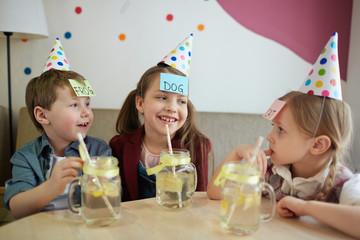 Group of kids having lemonade and playing humorous leisure game