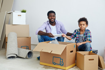 Happy young man and his son unpacking carton-boxes after moving to new flat