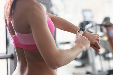 Young woman with fitness tracker in gym