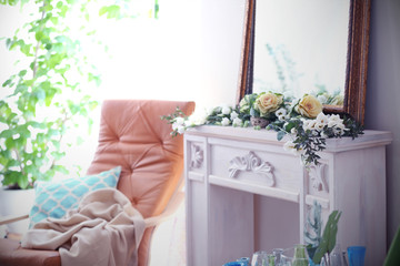 Interior of light room with beautiful flowers on mantelpiece