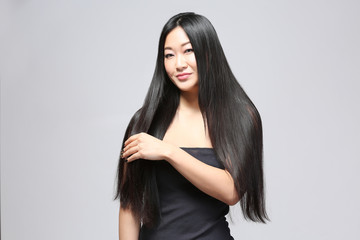 Beautiful Asian woman with long straight hair on light background