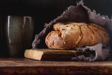 Fresh homemade French black bread. Dark background.