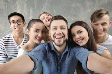 Happy young friends taking selfie near grunge wall