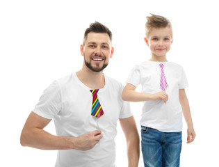Handsome man and his son with party decor on white background