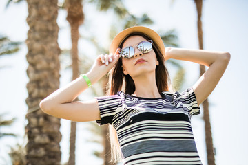 Cheerful young woman in hat and sunglasses hands over it in summer palms background. Summer vocation.