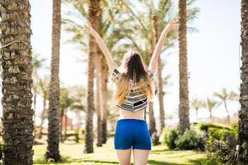 Back view of happy excited young woman with raised hands walking and enjoying on summer resort. Summer vocation.