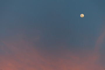 Pink cloud on sky with moon