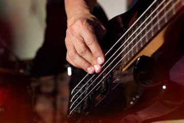 Bass guitar in hands of musician