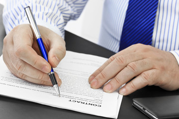 Businessman with pen analyzing contract at desk in the office