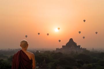 Monk looking at hot air balloons at sunrise at Bagan temple in Burma, Myanmar