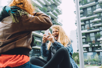 Two young women using smart phone outdoor taking photos - technology, social network, communication concept