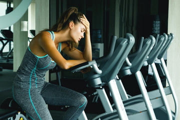 Woman in the gym with overtraining symptoms