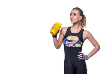 Attractive athletic woman relaxing after workout with shaker isolated over white background. Healthy girl drinks whey protein. Copyspace for text.