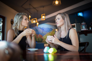 Close up image of two young girlfriends enjoying a cup of coffee in a trendy coffee shop