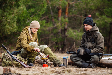 .Two hunters are eating together in the forest. Bushcraft, hunting and people concept