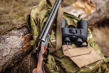 Set of military hunting equipment with rifle in forest during hunting season.