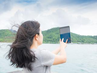 asian woman selfie with seascape against blue sky
