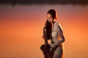 Beautiful  young woman playing the saxophone on during sunset,Thailand