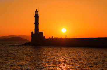 View of the lighthouse in the sea in Chania, Crete, Greece. Silhouettes against the setting sun.