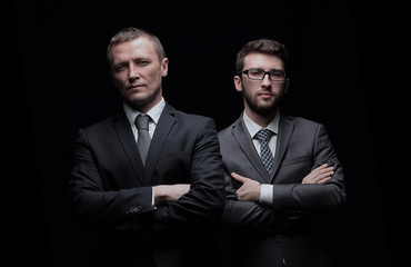Two serious businessmen with arms crossed isolated on black