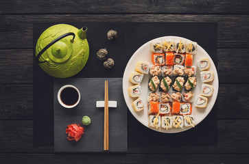 Set of sushi and rolls with teapot on black rustic wood, top view