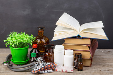 Medical education concept - books, pharmacy bottles, stethoscope in the auditorium with blackboard
