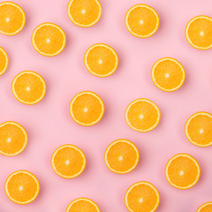 Colorful fruit pattern of fresh orange slices on pink background