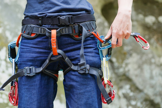 Female Climber with climbing equipment on the belt is ready to make her way up. Extreme sport