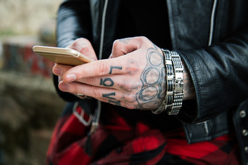 Tattooed man hands with smartphone