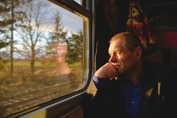 A man near a window on a train in the sun travels.
