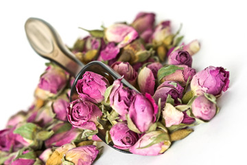 Pile of dried roses herbal tea on white background with spoon inside