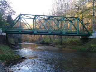 Bridge/Trestle spanning a deep and wide creek filled with water.