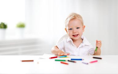 Happy baby boy draws with colored pencils.