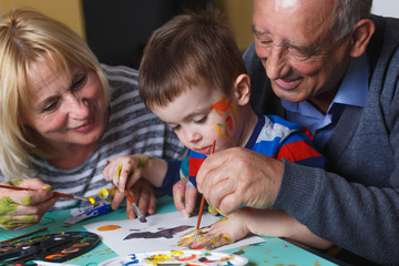 Grandmother and grandfather with grandson drawing together at home.