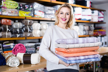 Young female customer boasting purchased home textiles