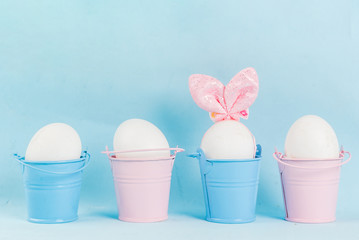 Ideas for holiday decoration. Easter. Eggs in a knitted cap with ears, looking like a rabbit. With a painted face. On a light blue background, in festive decorative multicolored buckets copy space