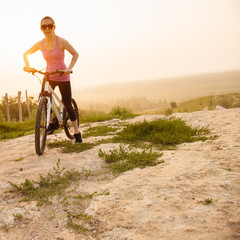 Girl on mountain bike rides on the trail on a beautiful sunrise.