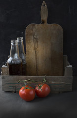 Still life of tomatoes, cutting board and bottles