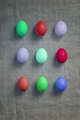 Pattern of Rows of colored easter eggs grey linen textured background. Easter web Background. Group of colored painted eggs. Happy Easter celebration concept. Template mock up with copy space for text