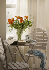 Flowers, table and chairs still life