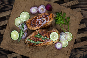 Grilled chicken filet with herbs  on a paper on wooden background. Rosemary and sliced lime on a dark groundwork.