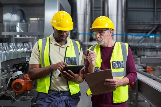 Two factory workers with clipboard and tablet