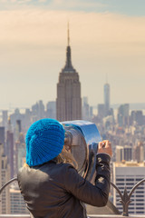 Wall Mural - Woman enjoying in New York City panoramic view. Manhattan downtown skyline with illuminated Empire State Building and skyscrapers seen from observation deck terrace.