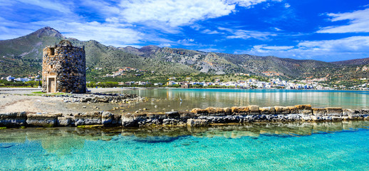 Pictorial scenery with old windmill and crystal waters in Elounda village, eastern Crete. Greece Fototapete