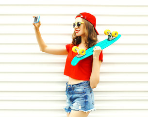 Fashion pretty cool smiling girl doing self portrait on smartphone over white background