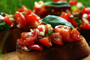 Tasty savory tomato Italian appetizers, or bruschetta, on slices of toasted baguette garnished with basil