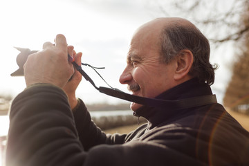 An elderly man with a mirrorless camera chooses a frame on nature